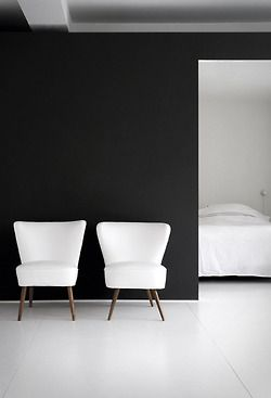 Simple white chairs, black and white walls— great example of minimalist design.