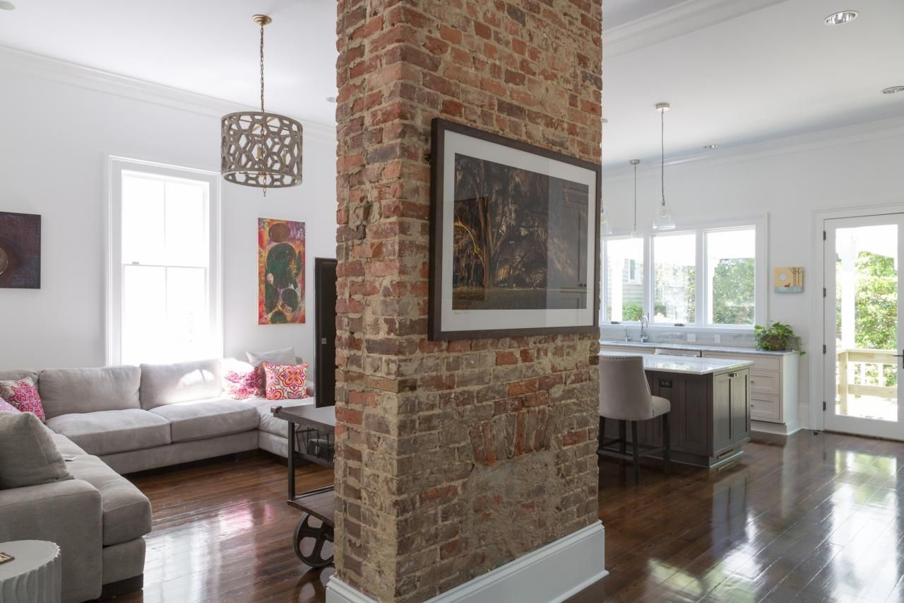 A red brick column makes a stately anchor in this open - Columns in living room ideas ...
