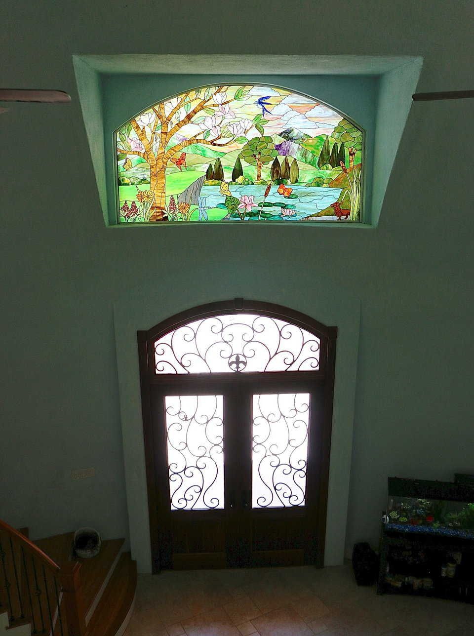 The stained glass window above the front door of the ...