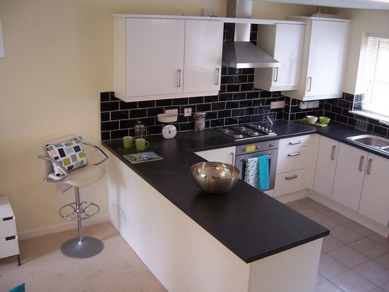 High Quality White Kitchen, Black Worktop And Splash Back