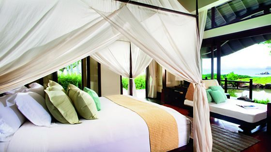 four poster bed with a white canopy in an airy bedroom featuring expansive windows and