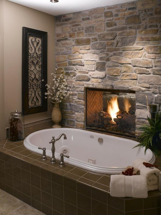This rustic feel bathroom houses a stone fireplace and brown tile wrapped soaking tub in cozy quarters.