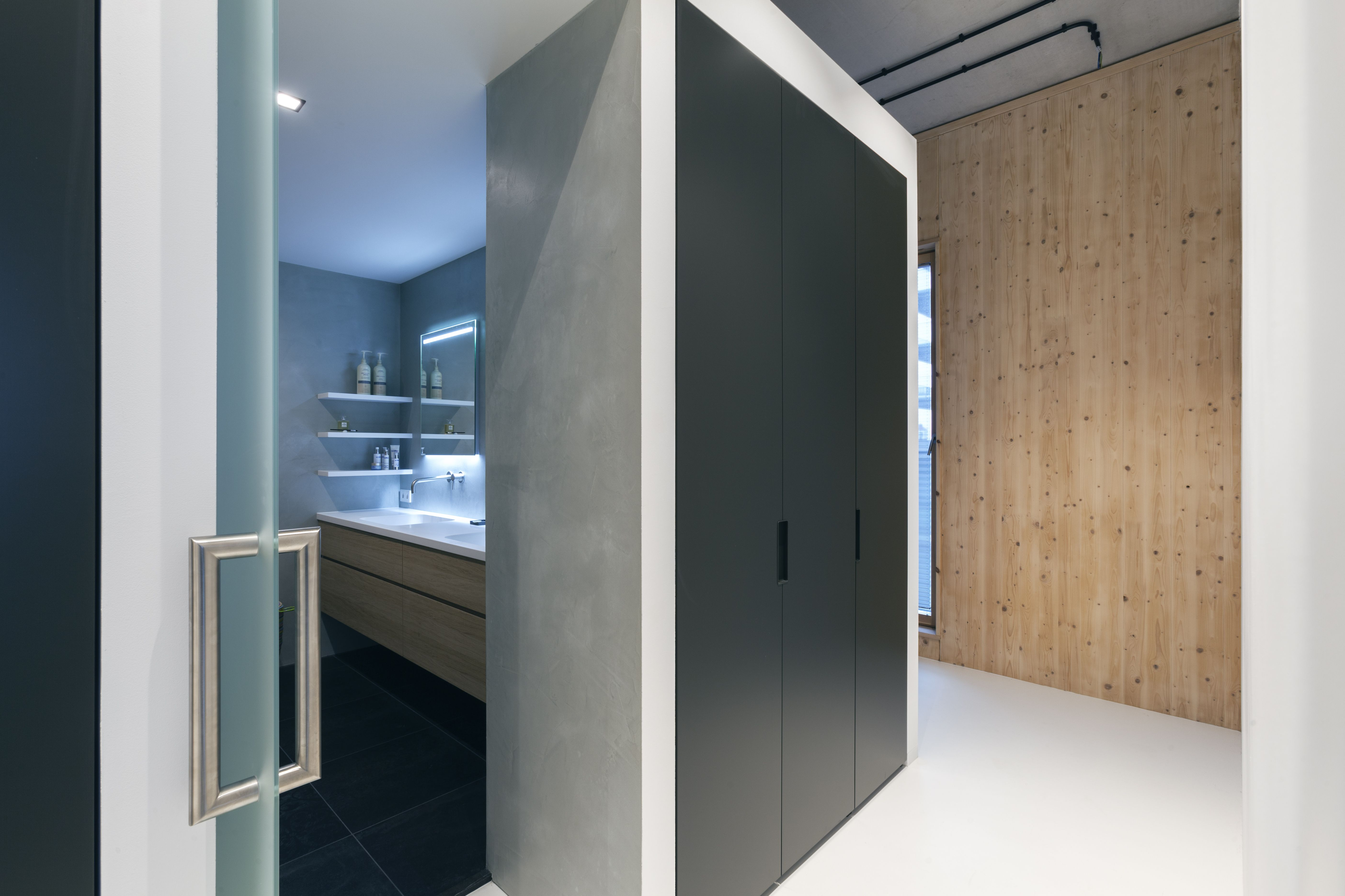 Strakke Badkamer Wanden : Inkijkje vanuit inloopkast naar strakke badkamer met deur van mat