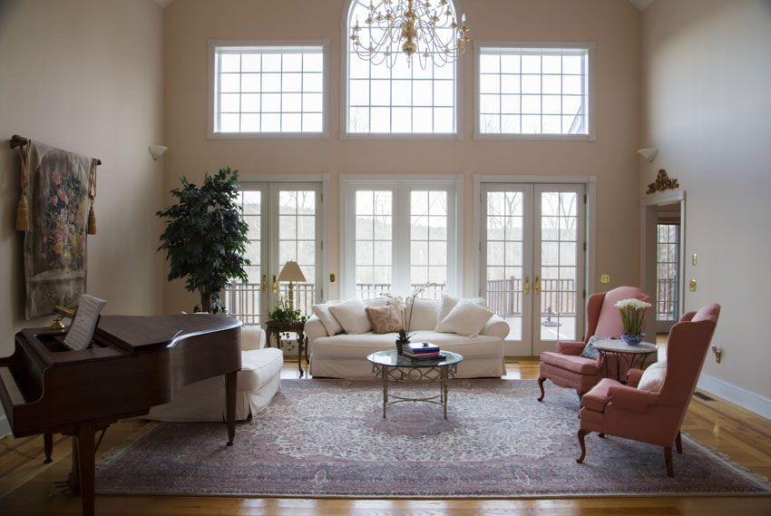 Formal Living Room With High Ceiling Wood Flooring And Grand
