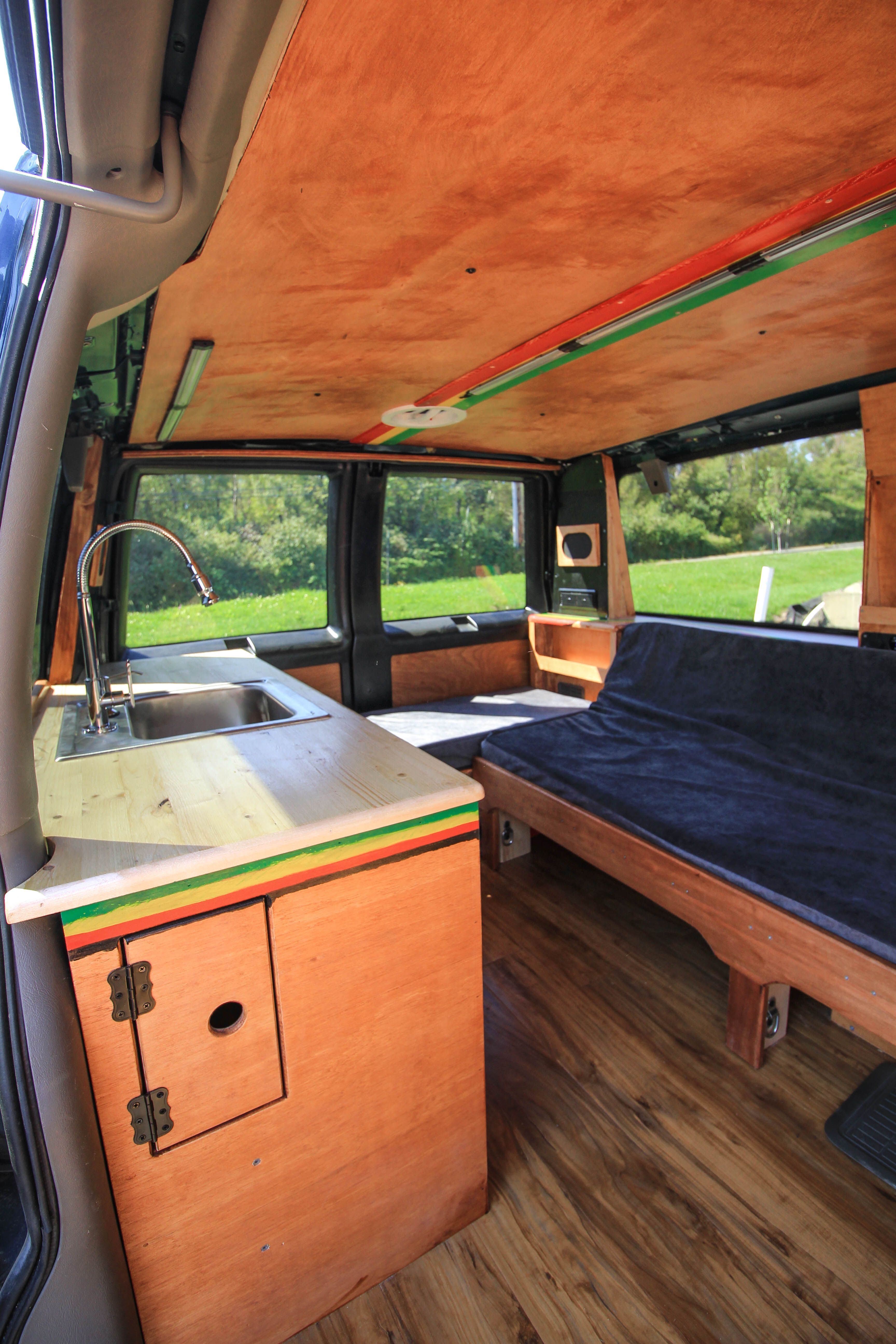 Could you live in an ultra-small space? Check out this rasta-themed Astro Van conversion by Freedom Vans! #van #vanlife #smallspace #tinyhouse #tinyhome #tinyliving #astrovan #chevyastro #kitchen #kitchenette #freedomvans #vanconversion #convertedvan #convertedastro