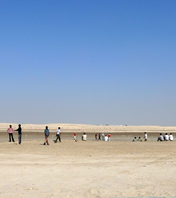 Abu Dhabi. Workers playing cricket on a Friday afternoon in the desert surrounding the new housing compounds.