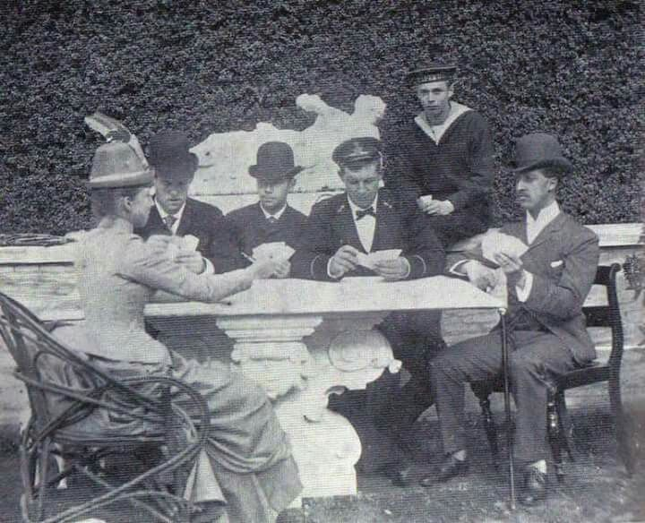 Royal cousins playing cards from left, Princess Louise of Wales, Crown Prince Constantine of Greece, Tsarevich Nicholas of Russia, Prince George of Greece and Denmark, Grand Duke George of Russia, Prince Albert Victor of Wales (Denmark ca1888)