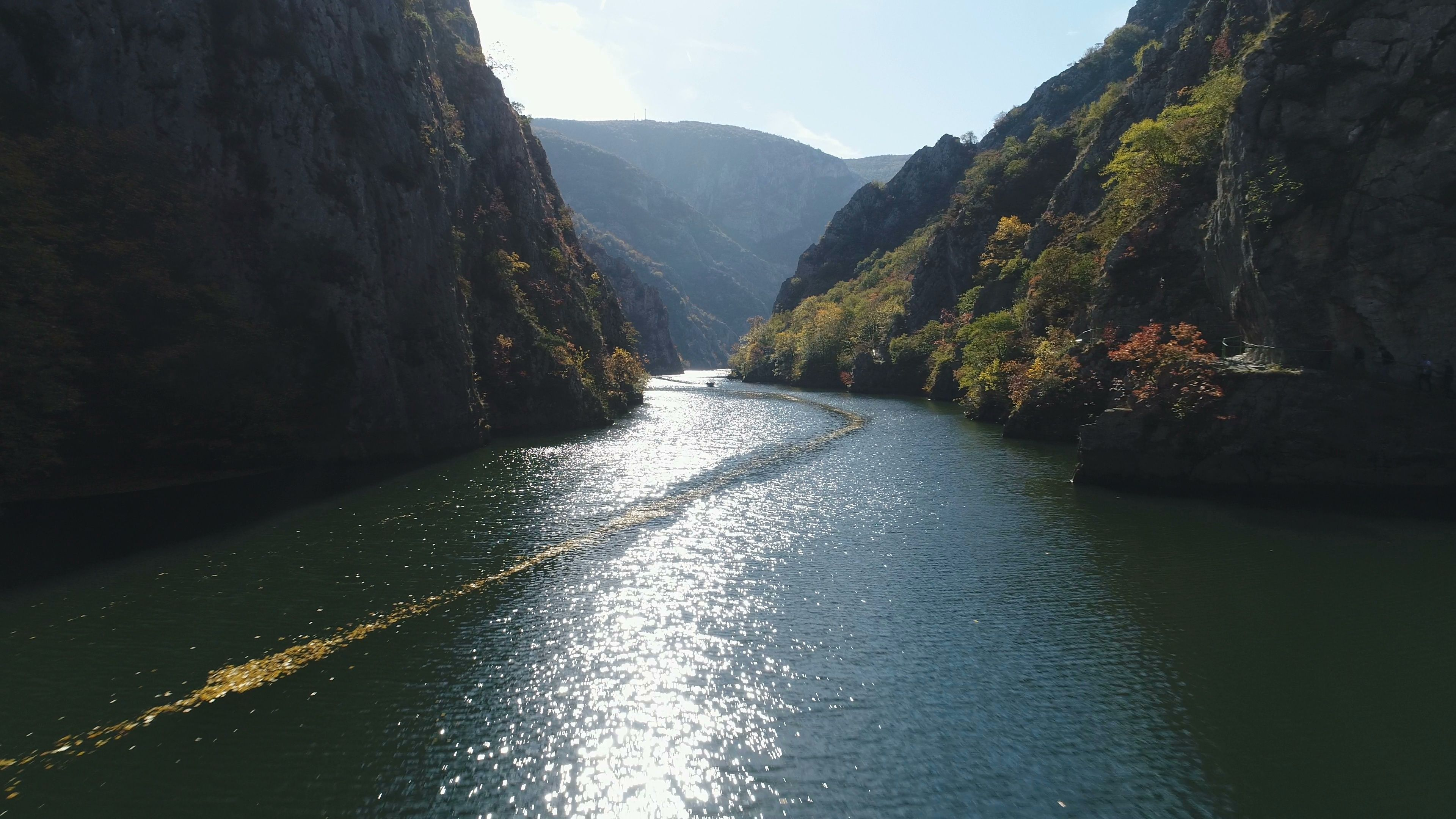Drone flight of small boat sailing through matka canyon in