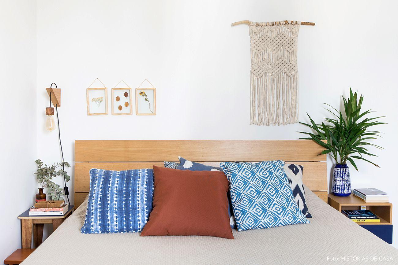 1eab63d7cd05 Quarto de casal tem cama de madeira, almofadas nas cores azul e ocre e  macramê na parede.