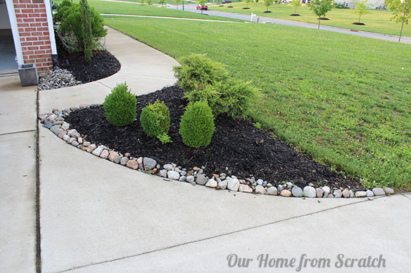 Protecting mulch beds with a stone perimeter flower for Installing river rock landscaping