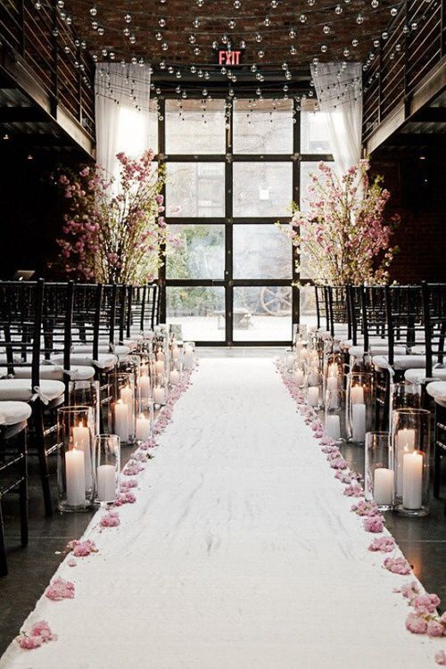 Candle And Rose Petal Lined Wedding Aisle With Flowering Branches At The Altar