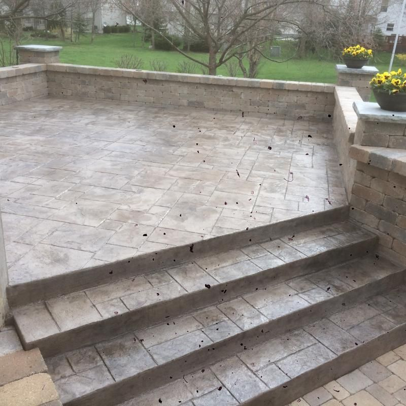 Raised stamped concrete patio with walls and lower paver ...
