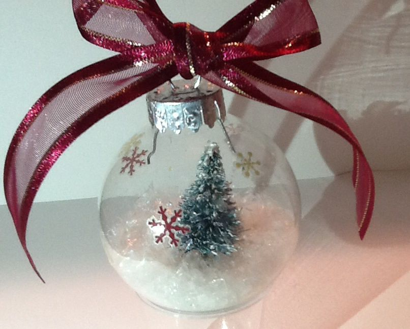 Iridescent snow with a snow covered miniature tree in a small glass Christmas bulb