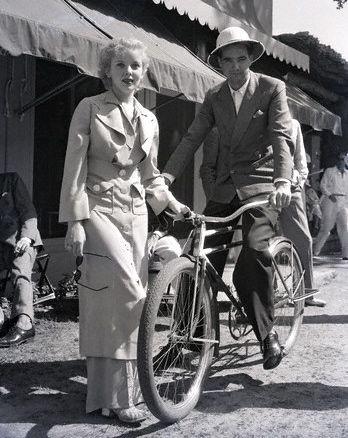 Howard Hughes rides a bike. Ida Lupino stands by.  55eecf2eb