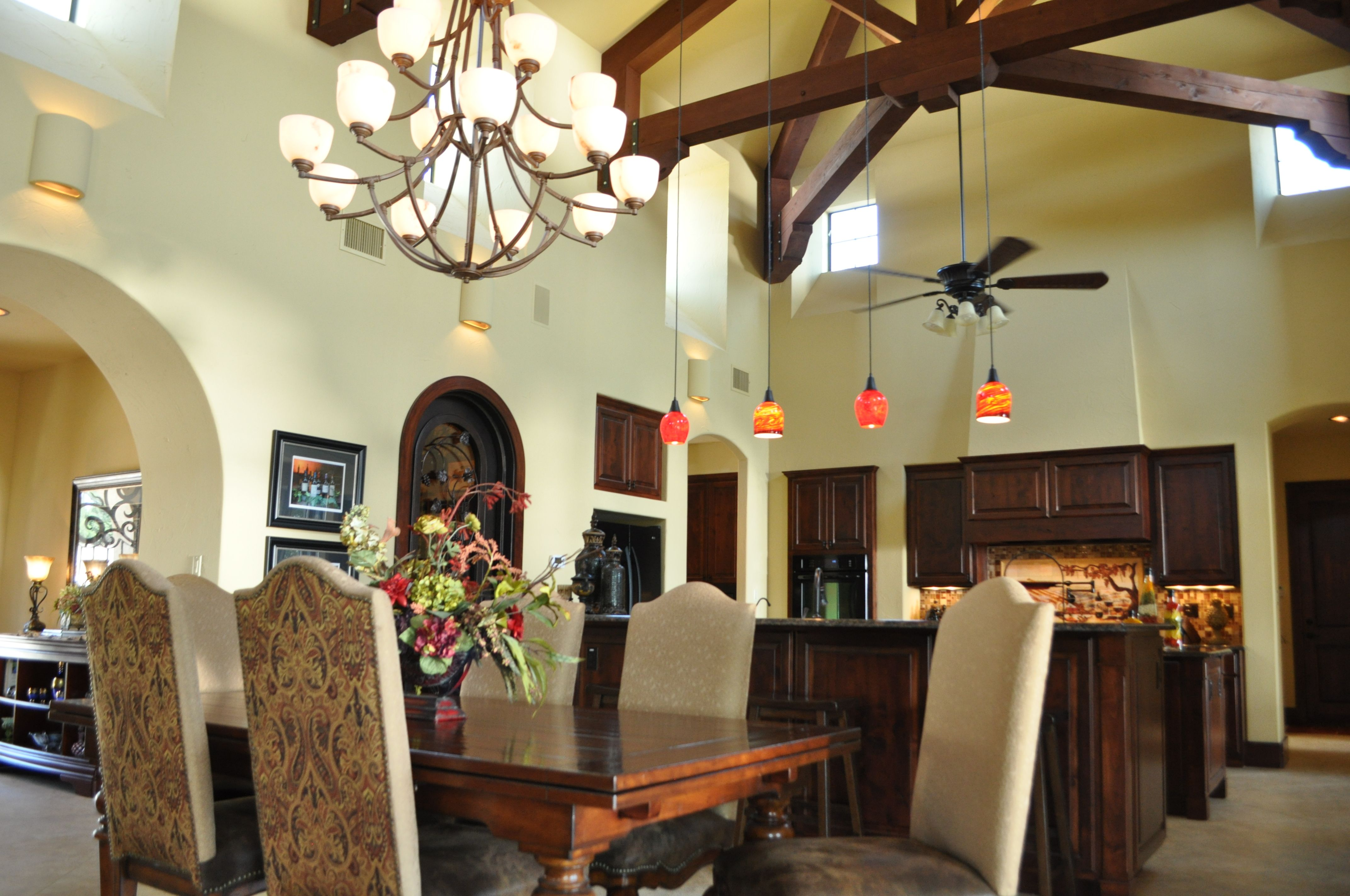 The chandelier and dining table define the dining area in the great room of this Tuscan style ...