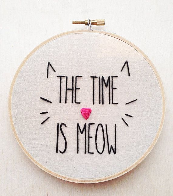 The phrase The Time is Meow with an outline of a cat is embroidered by me with embroidery floss on 100% cotton muslin fabric into a 5 embroidery
