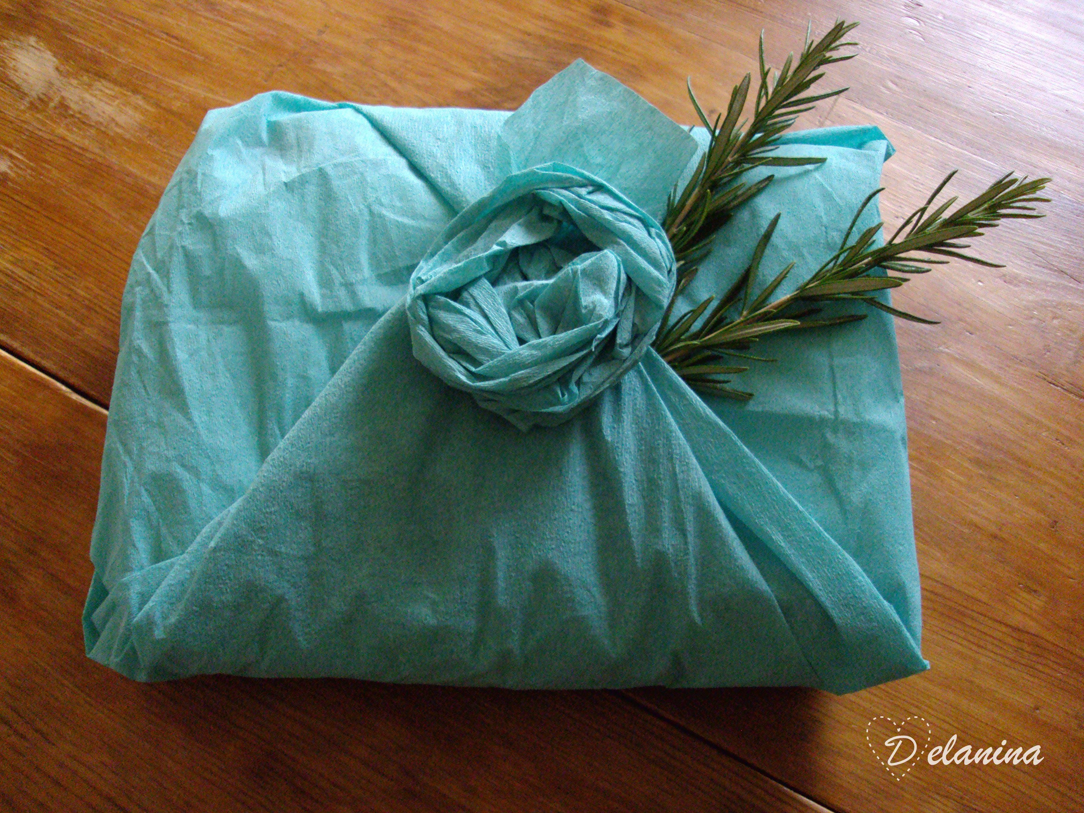 Empaquetado con papel pinocho azul turquesa y ramita de romero natural.