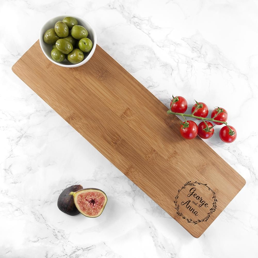 Showcase your love with our Personalised Couple's Wreath Serving Board and celebrate your favourite couple with this gorgeous gift! The ideal gift for anniversaries, weddings, or Valentine's Day, this serving board is the perfect finishing touch to your home. Our serving boards are made from bamboo, a fast-growing wood that's always renewing itself, so it's sustainable as well as stylish! Bamboo also has natural anti-bacterial properties, making it a great material for kitchenware. Choose two na
