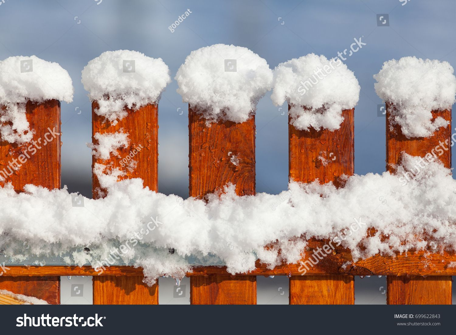 detail of a new wooden garden fence covered with fresh snow in
