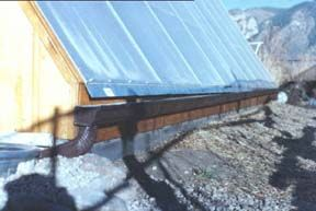 One long continuous gutter collects water off the glazing wall and delivers it to a 120 gallon stock tank
