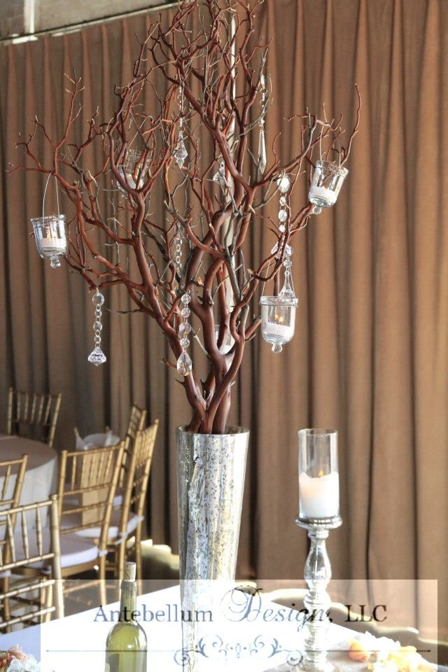 tall natural manzanita branches in a tall silver mercury vase with crystals and candles by