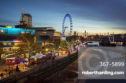 Christmas market is on the South Bank with Big Ben, Houses of Parliament and London Eye at dusk behind, London, England, United Kingdom, Europe