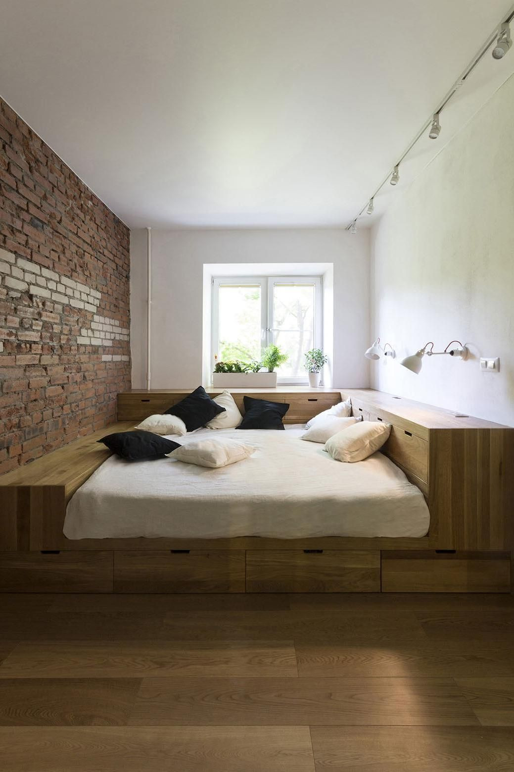 terrific exposed brick bedroom wall ideas   a terrific wooden bed podium with modern cream bedding and ...