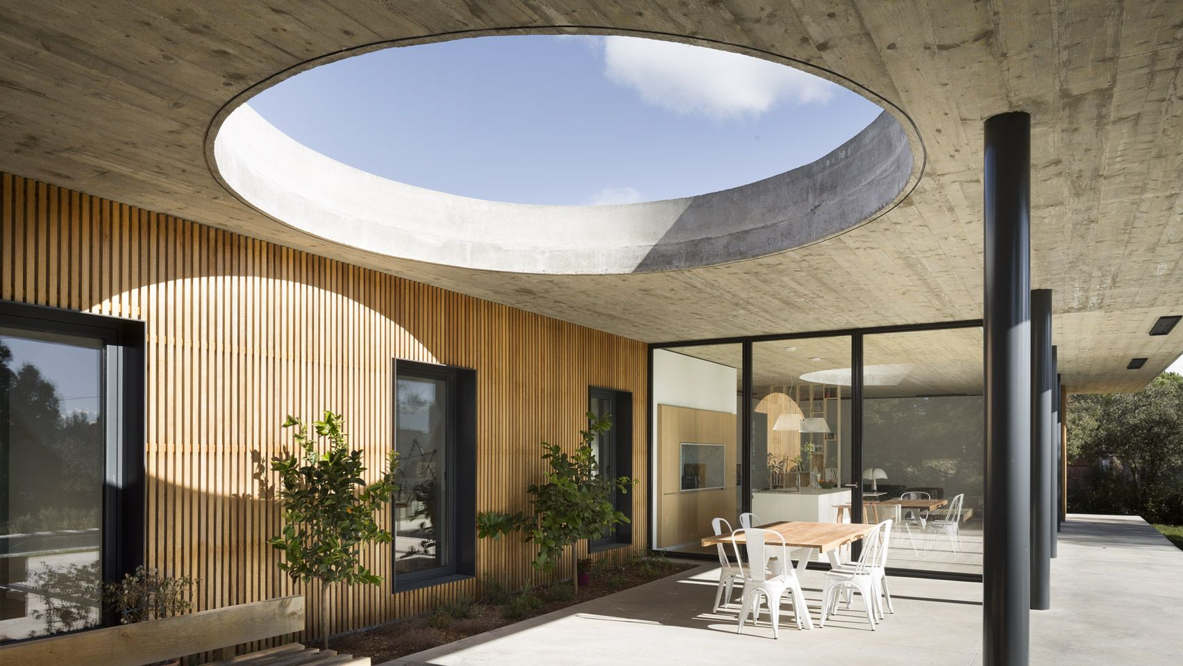 A Huge Round Opening Is Carved Above The Outdoor Dining Area Of This House In Southern France By Pasc Concrete Houses Skylight Architecture Architecture House