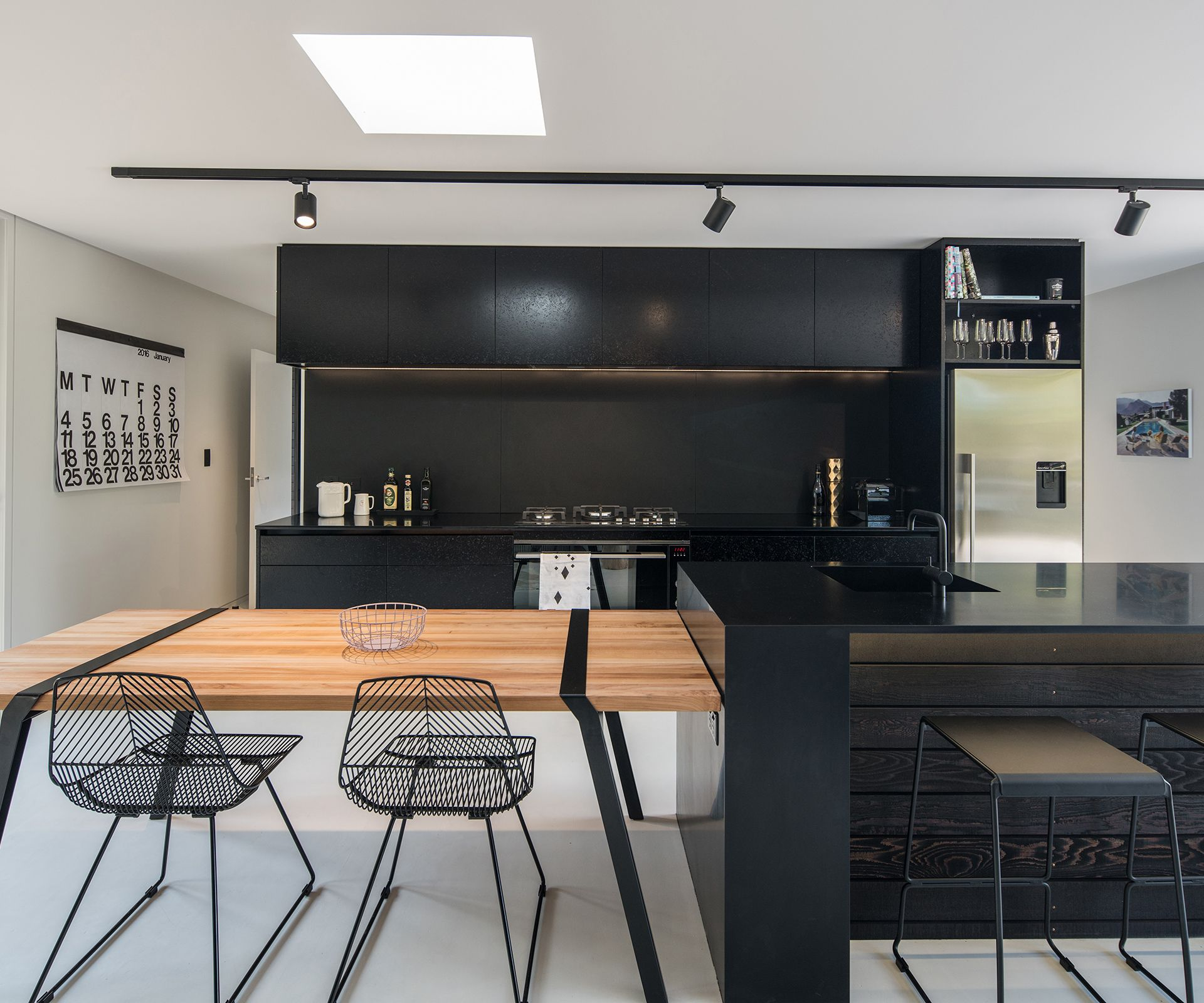 The blackandwhite kitchen also features a movable table adjacent