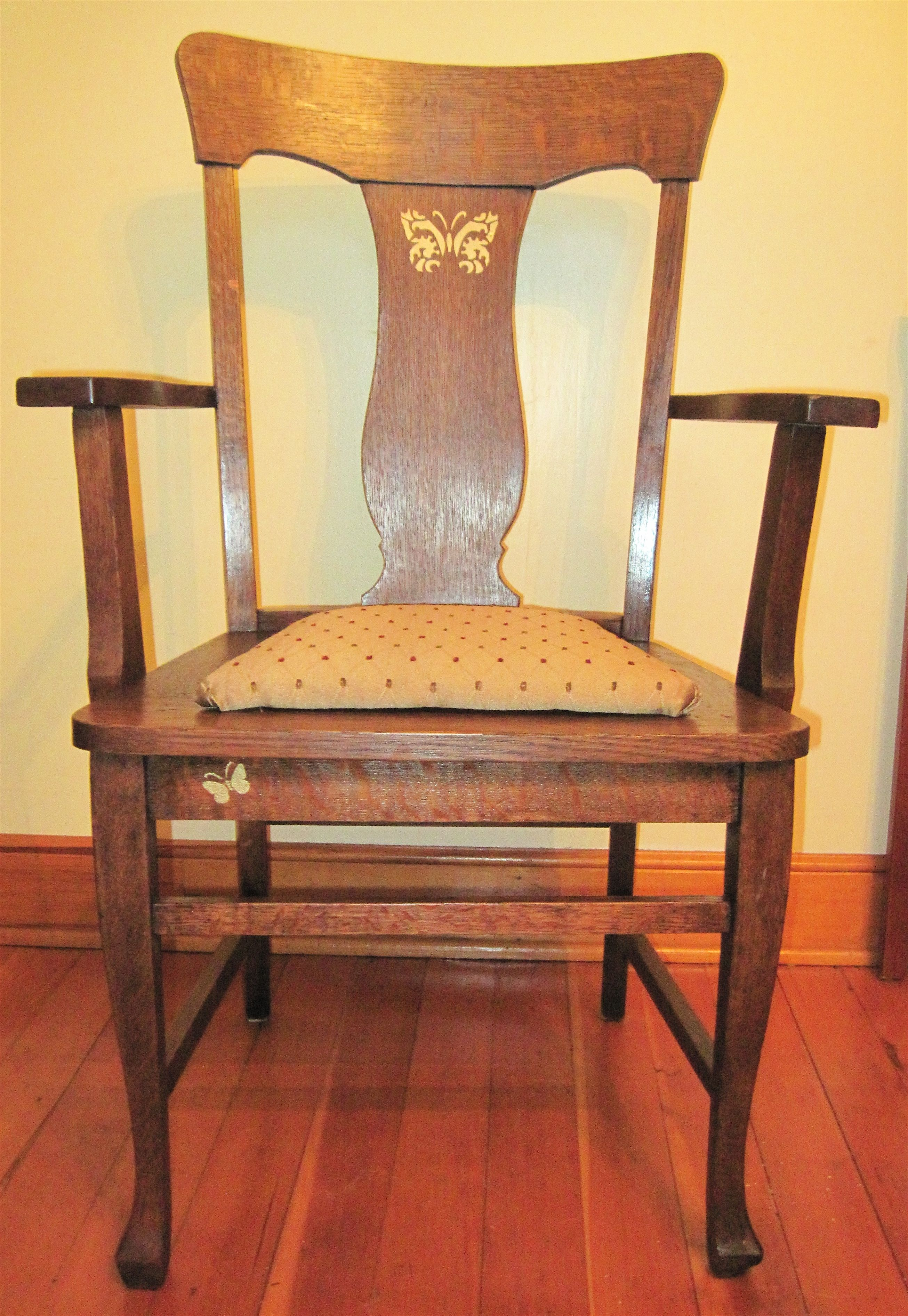 Refinished large old oak armchair.  New satiny fabric, and small, elegant golden butterflies stenciled on each  side.  This is a large, sturdy and beautiful chair.  For sale for $99.