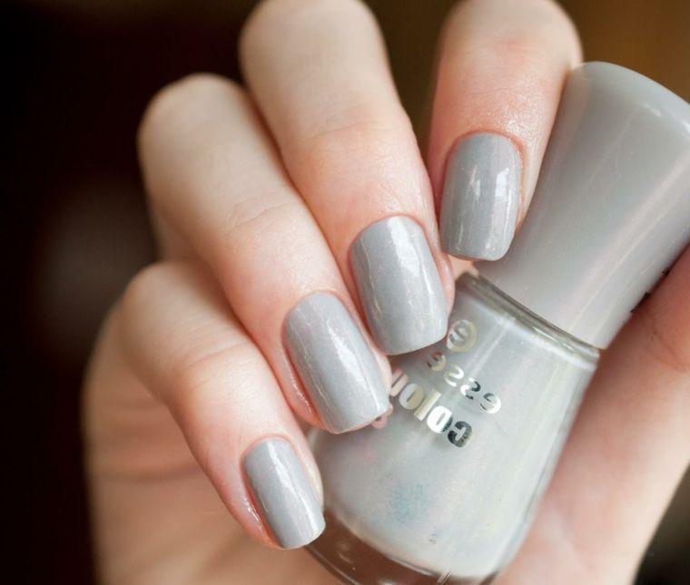 Unghie gel bellissime di colore grigio effetto lucido, bottiglietta di  smalto tra le mani