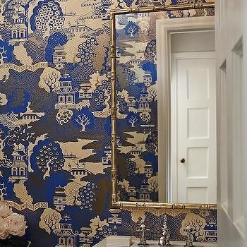 White and blue powder room features walls clad in trim molding framing blue chinoiserie wallpaper lined with a silver pagoda mirror over carrera marble top