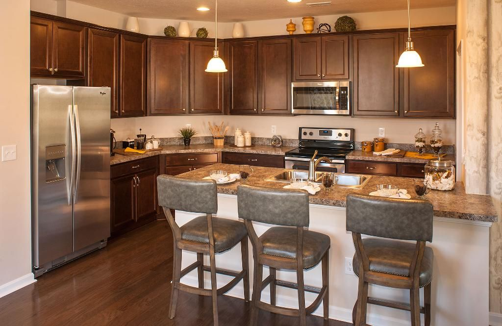 Kitchen With Dark Cabinets An Island And Hardwood Floors The Calabasas Floor Plan Drees Homes Hardwood Floors In Kitchen Kitchen Decor Dark Kitchen Cabinets