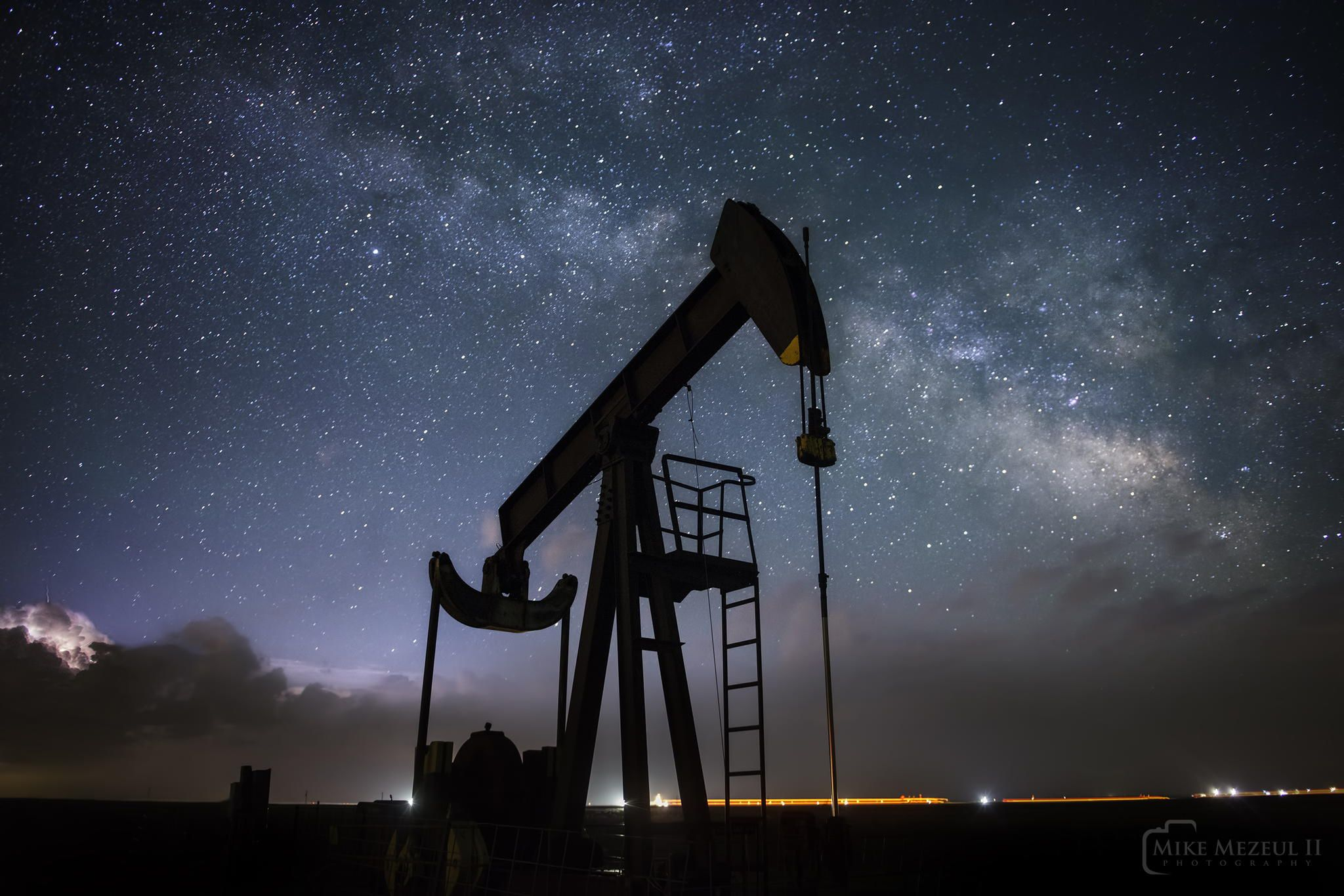 An oil pumpjack beneath the Milky Way and a distant lightning storm. by Mike Mezeul II on 500px