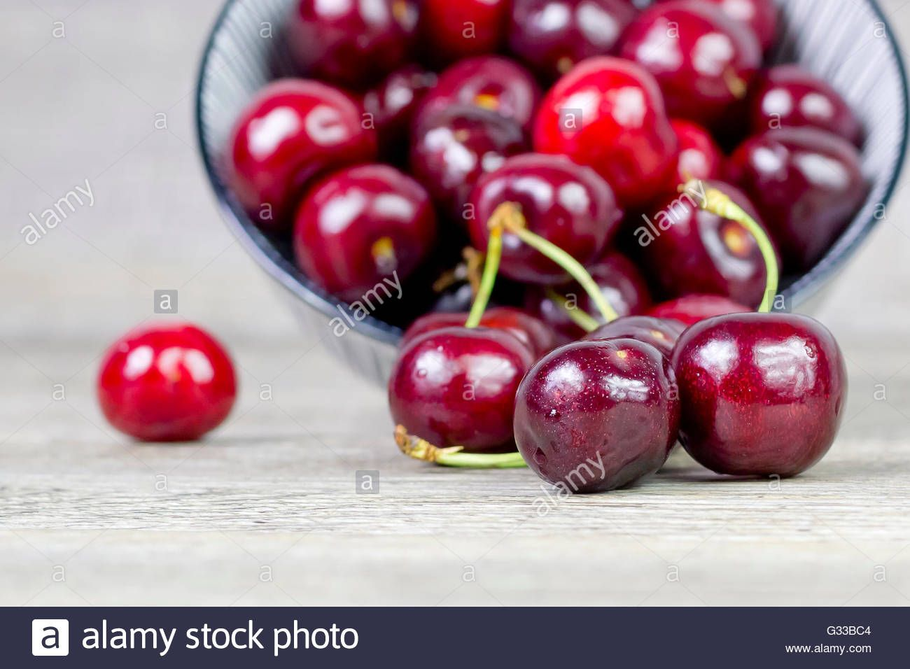 Download this stock image: Cherries on a wooden surface - G33BC4 from Alamy's library of millions of high resolution stock photos, illustrations and vectors.