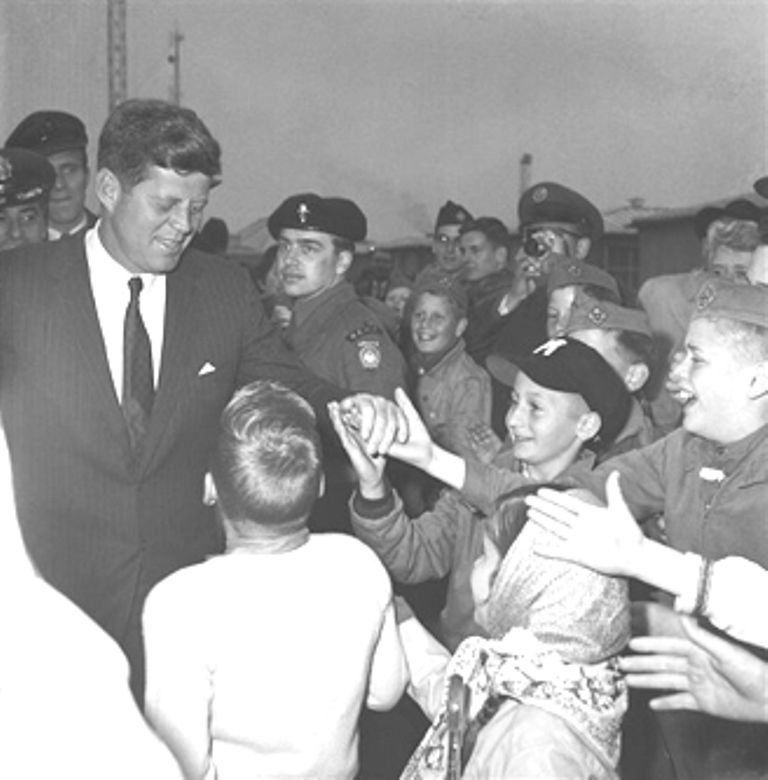 1961. 2 Juin. President John F. Kennedy grasps outstretched hands of childern of SHAPE servicemen during his visit there