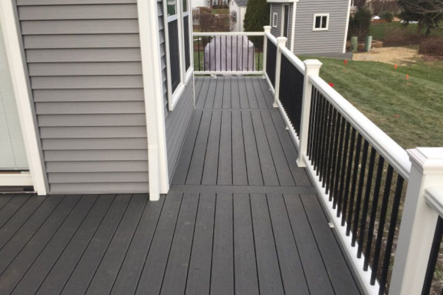 Clam Shell Trex Deck With White Transcend Railings With Black Aluminum Balusters Barrington Rock Solid Builder Trex Deck Patio Deck Designs Trex Deck Colors
