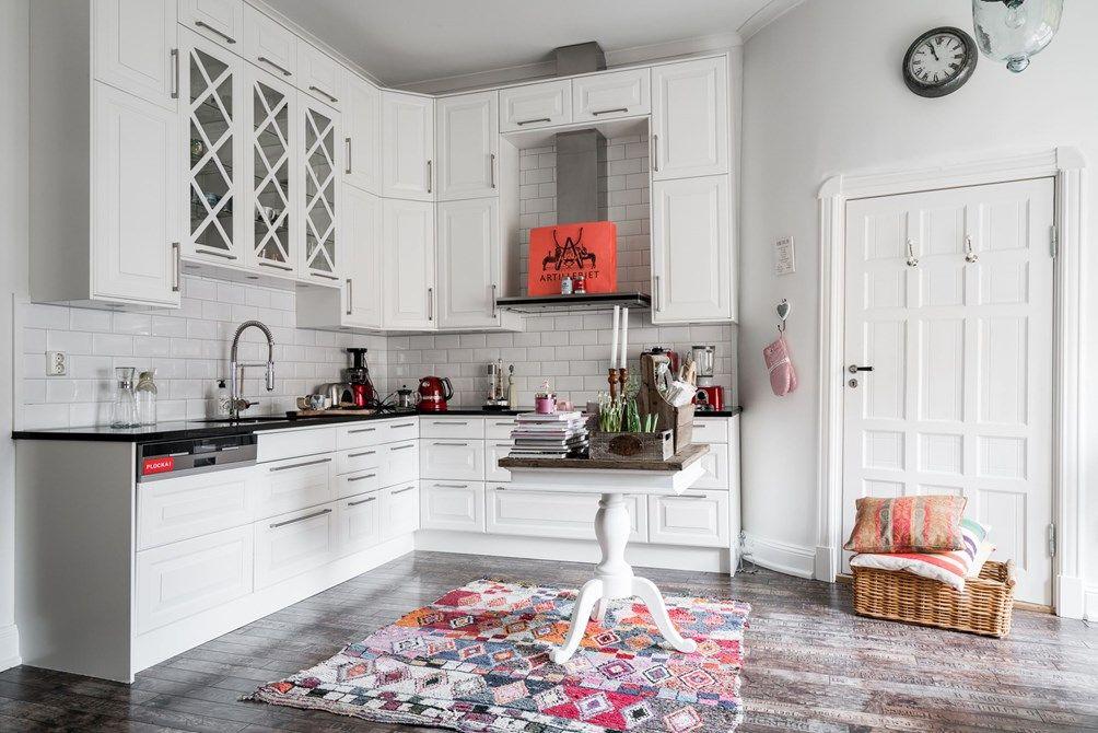 Vitt kök med mycket skåp och lådor för bra förvaring och exklusiv svart bänkskiva i granit