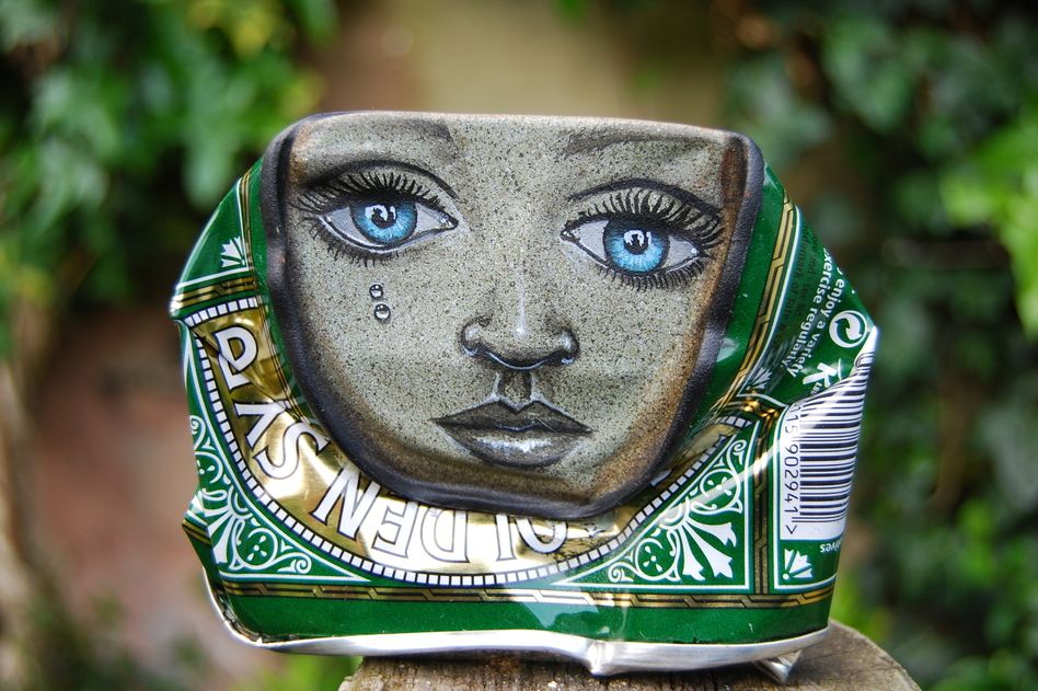 A lady face painted on a Lyle's Golden Syrup can.