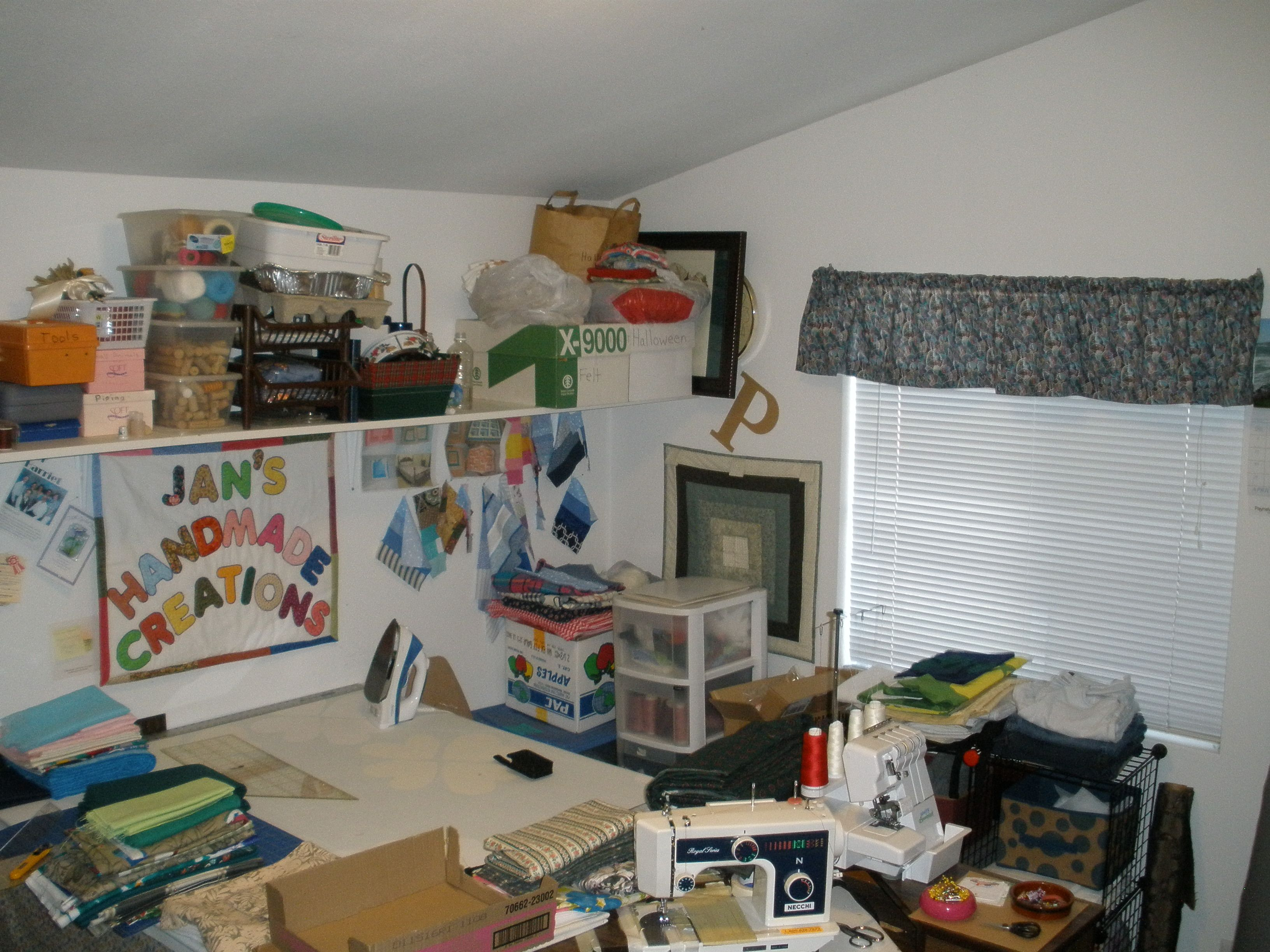 Shelf full with seasonal craft kits, antique quilt tops, drummel, tool box, piping, small plastic animals, thread, boxes of wine cork, cotton yarn, and bags full of more seasonal items. White bag is a cork wreath and a cross stitch picture. Can you see the clock peaking out from behind the frame? Below that is a small hanging quilt. On the table, more fabric, my #1 sewing machines and my serger. My fabric is on an open shelf to the right of the window, so I keep the shade closed.