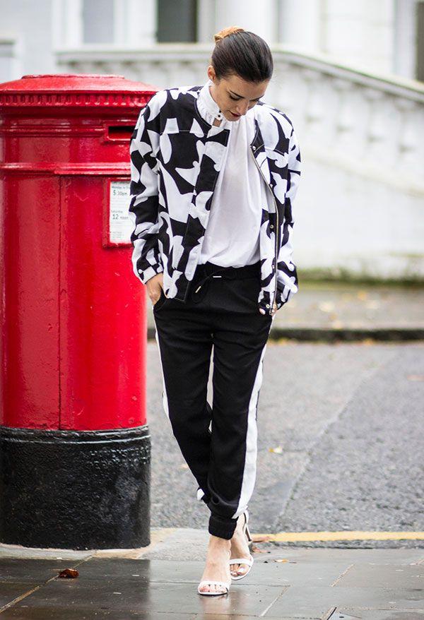 Anisa Sojka com look sportswear com jaqueta bombar preta e branca e calça jogging