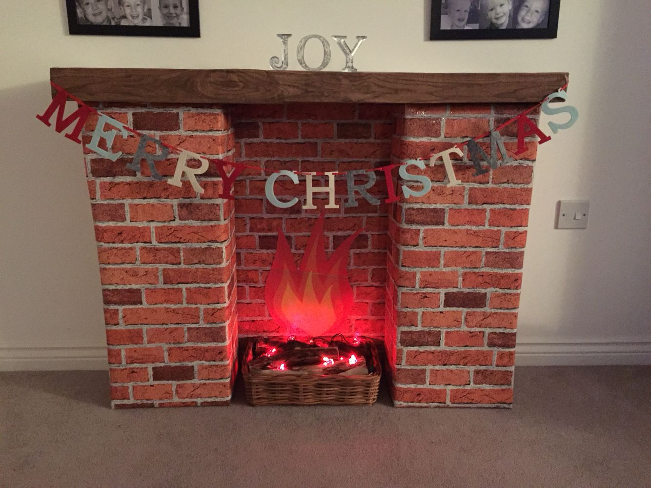 Homemade Christmas Fireplace. Cardboard boxes covered in brick wallpaper  and wood effect vinyl.
