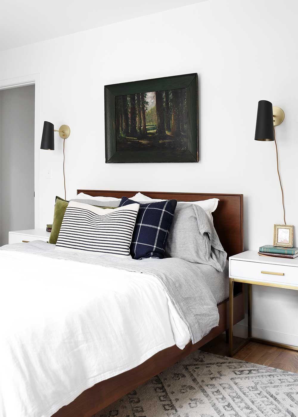 A minimal masculine master bedroom with linen, brass, deep
