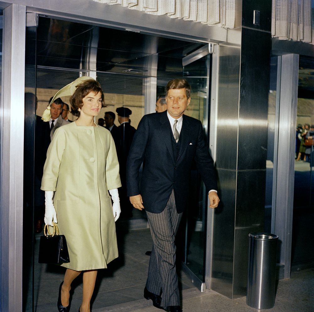 """Date(s) of Materials: 16 March 1961     Photographer:  Knudsen, Robert L. (Robert LeRoy), 1929-1989    Description: Ceremony celebrating the Unification of Italy. First Lady Jacqueline Kennedy and President John F. Kennedy (with a cut above his left eye), walking through doorway; White House Secret Service Agent, Gerald """"Jerry"""" Behn (behind the First Lady); others unidentified. State Department, Washington, D.C."""