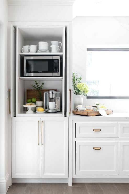 Kitchen coffee station hidden by fold-in white shaker cabinet pocket doors. #whiteshakercabinets