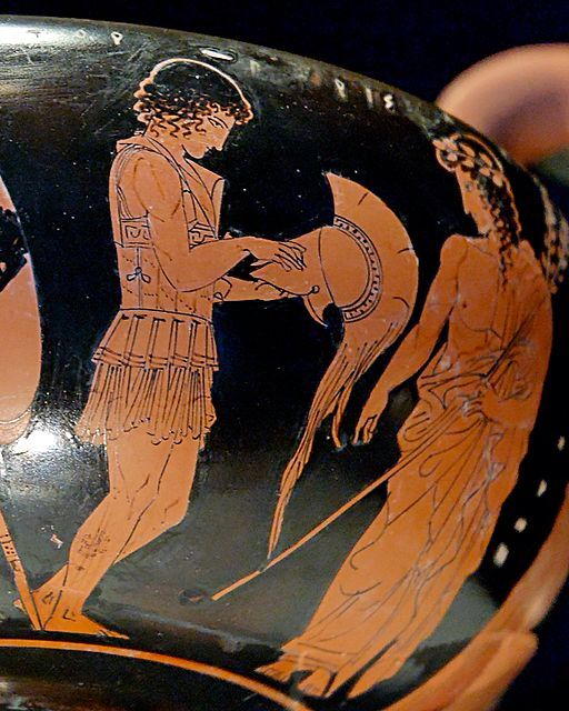 Paris (on the left) putting on his armour as Apollo (on the right) watches him. Attic red-figure kantharos.