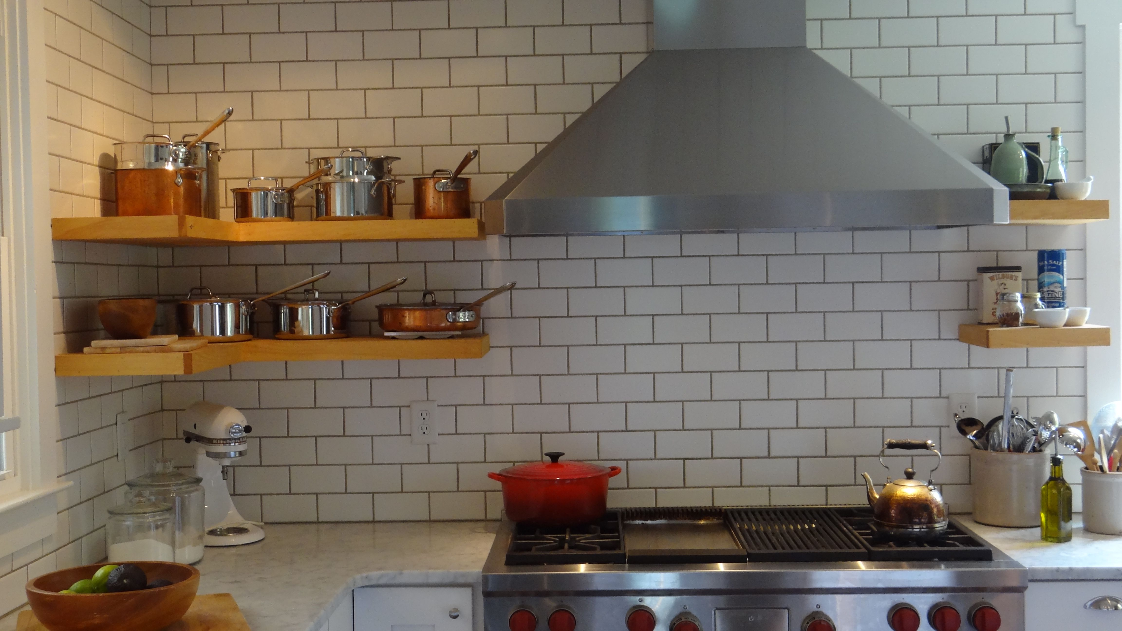 Open pine shelving and white subway tile the full height of the wall.