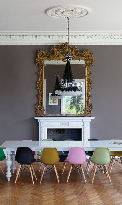 Same style chairs, all a different hue. Genius! The rooms feels eclectic and yet harmonious and yet off balance with the juxapostion of that  mirror which  is too big over a mantle that is too small. Focus is immediately off the dining table