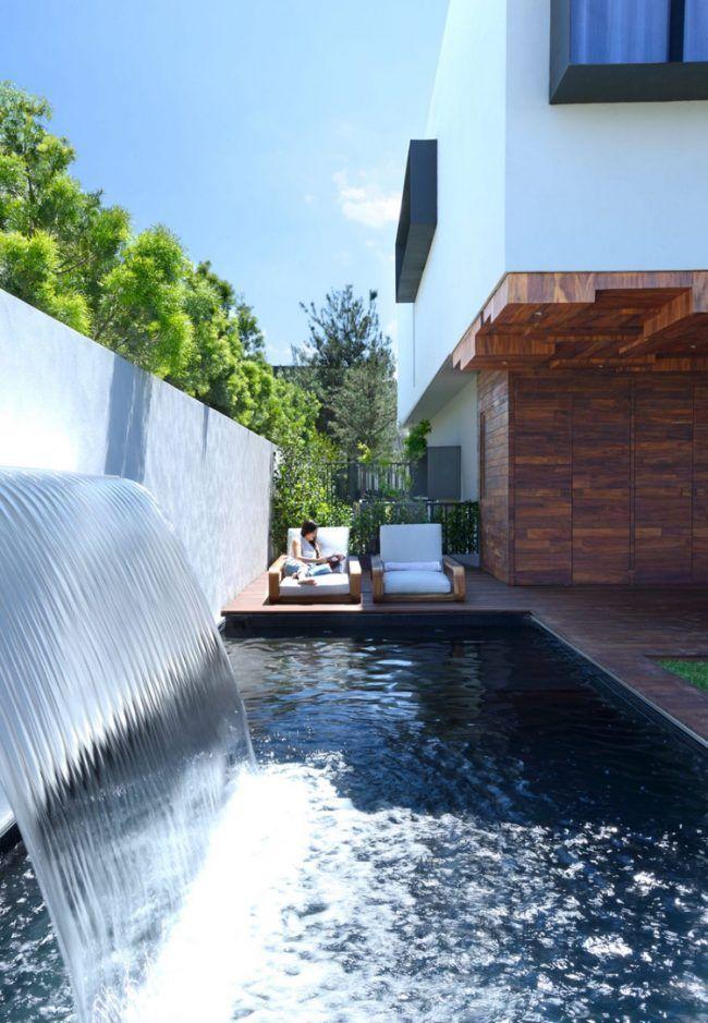 dunkles-holz-terrasse-bodenbelag-sonnenliegen-pool-wasserfall