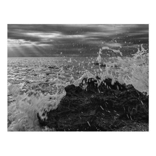 Postal de una ola chocando contra la roca en blanco y negro